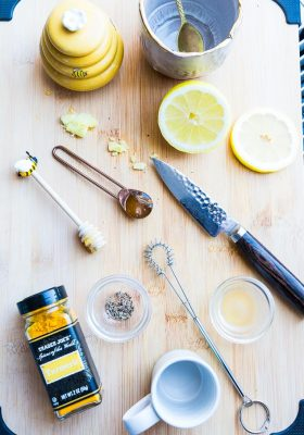 Top view of ingredients to make an immunity boosting shot - turmeric, honey, black pepper, lemon and apple cider vinegar