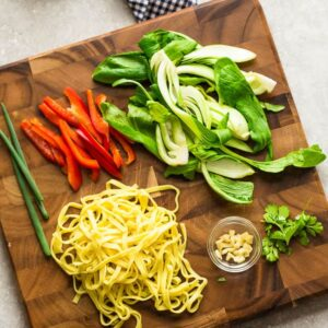 Top view of chow mein ingredients on a cutting board: green onions, red bell peppers, bok choy and egg noodles