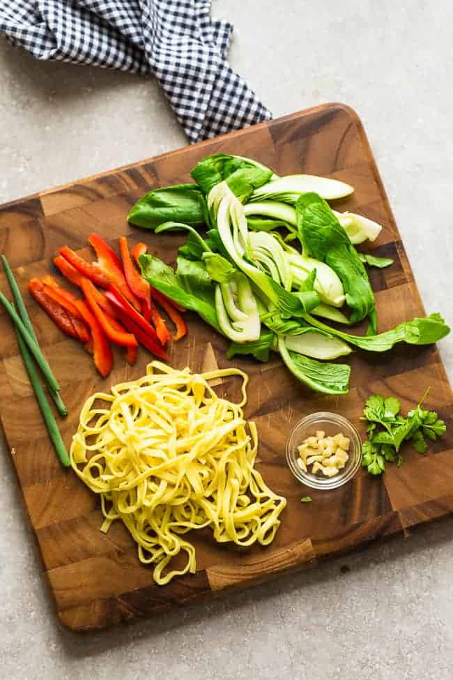 Top view of bok choy, red bell peppers, egg noodles, and other ingredients needed for making Chicken Chow Mein on a wooden cutting board