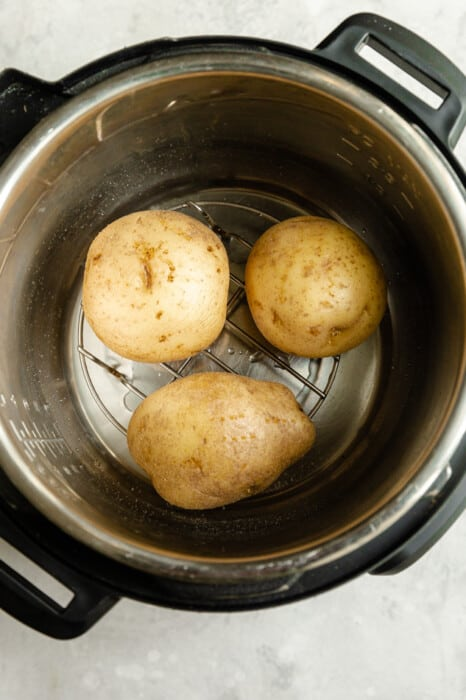 3 potatoes on a rack in an instant pot