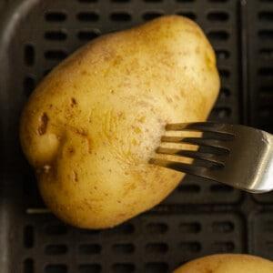 A fork poking a potato