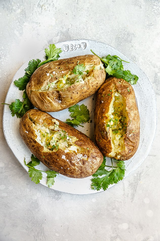 Overhead view of 3 baked potatoes cut open on a plate with fresh herbs