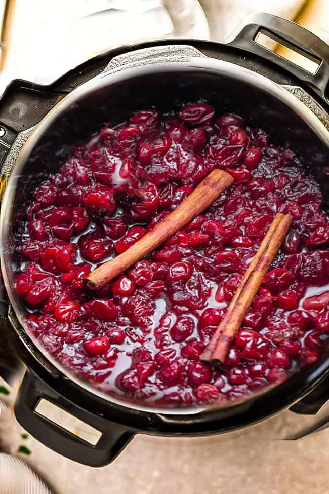 Cooked cranberry sauce in an Instant Pot pressure cooker with cinnamon sticks