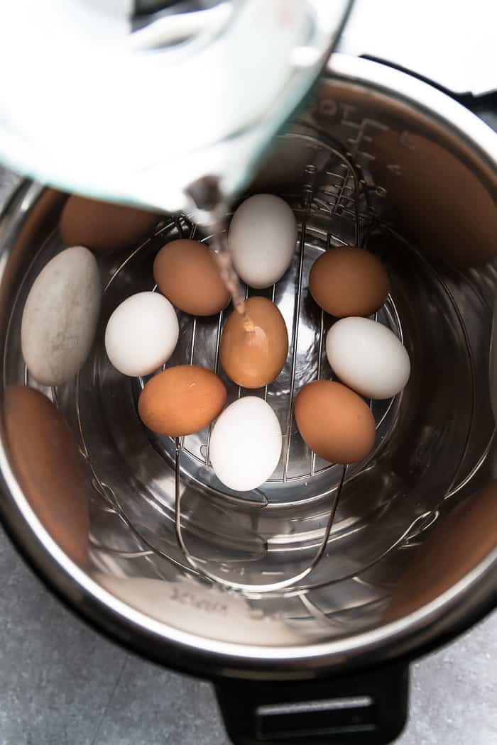 pouring water into an electric pressure cooker over whole eggs to make Instant Pot eggs