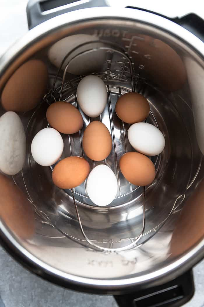 unpeeled brown and white eggs in a pressure cooker, ready for cooking