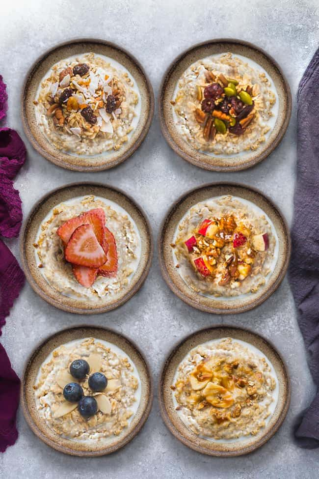 Top view of six steel cut oats bowls with different toppings on a grey background and napkins