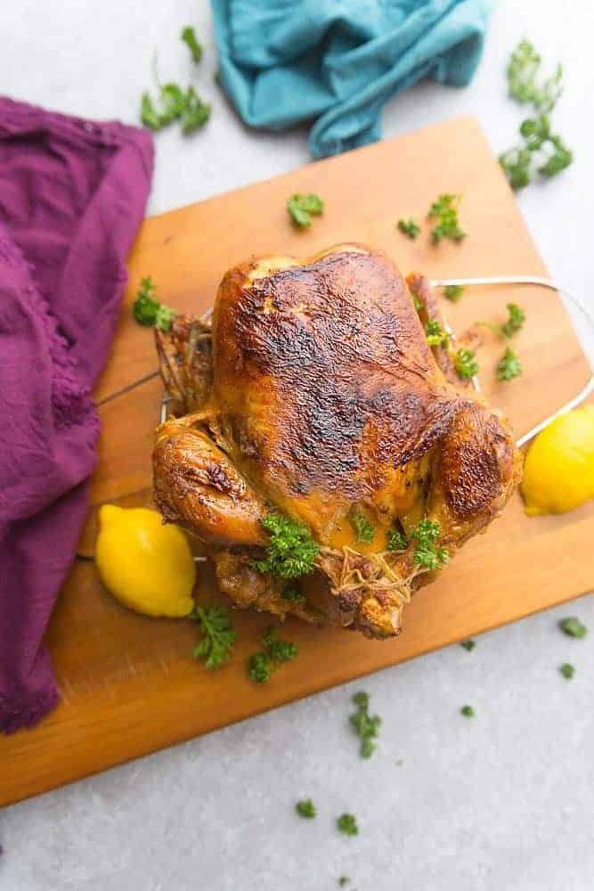 golden crispy skinned whole chicken cooked in an Instant Pot sitting on a cutting board