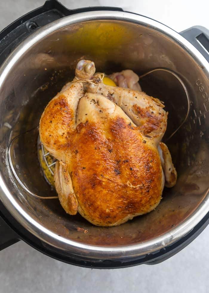 whole fryer chicken sitting in an electric pressure cooker