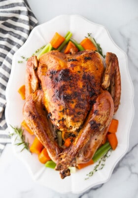 Top view of Instant Pot Whole Turkey on a white platter with vegetables