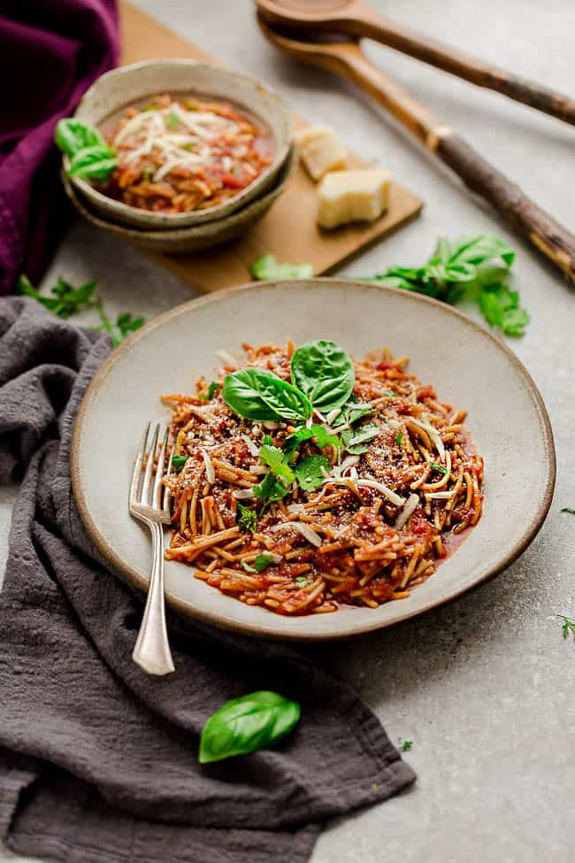 Two Bowls of Spaghetti with Meat Sauce on a Countertop with Cloth Napkins