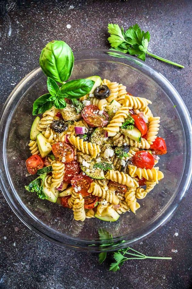 This Easy Italian Pasta is the perfect side dish for summer barbecues, potlucks, parties and cookouts. Best of all, you can customize the add-ins with what you have on hand. This recipe includes cherry tomatoes, zucchini, olives, feta cheese, onions, chopped kale and some fresh herbs like parsley and basil. A homemade Italian dressing makes this even more delicious!
