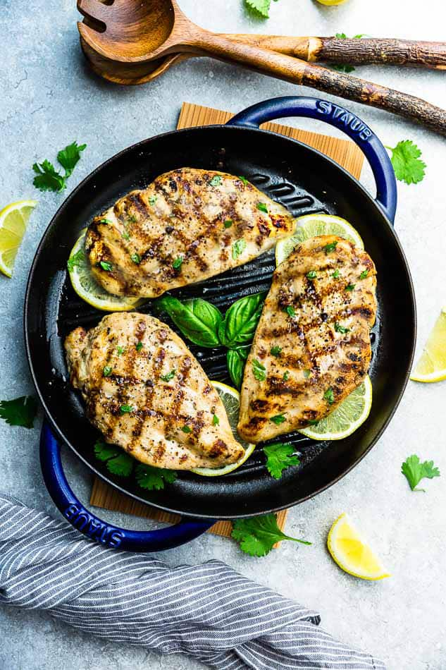 Top view of three grilled chicken breasts in a grill pan on a grey background
