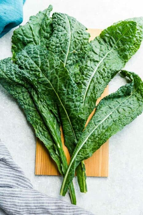 Top view of kale leaves on a wooden board on a grey background