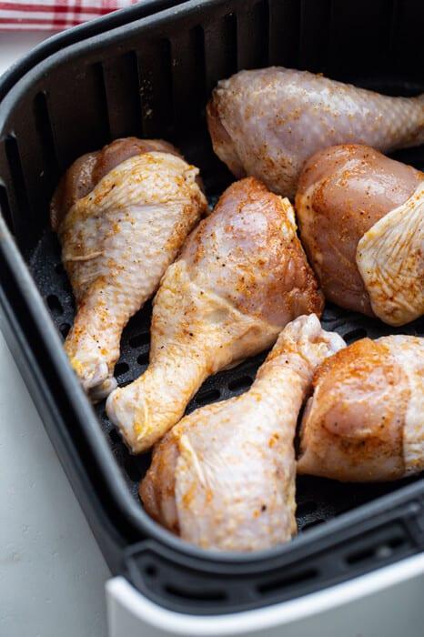Six raw chicken drumsticks in an air fryer basket