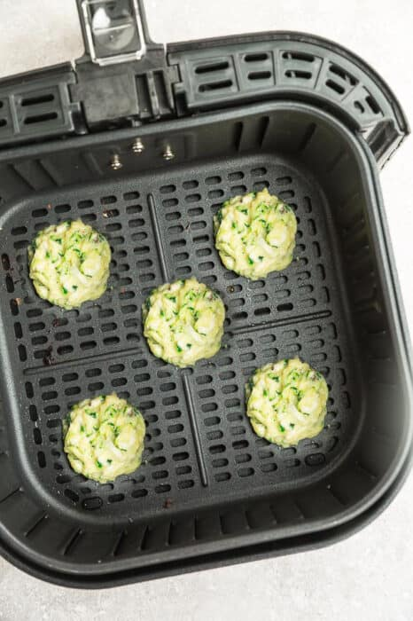 Top view of zucchini fritter batter in an air fryer basket
