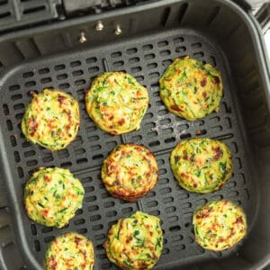 Top view of cooked crispy zucchini fritters in an air fryer basket