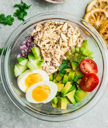 Top view of ingredients to make an avocado chicken salad in a large clear bowl on a grey background