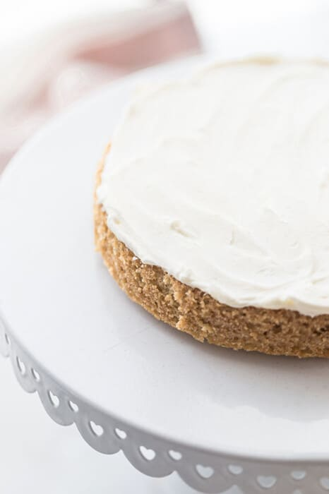 A round Keto Vanilla Cake layer topped with frosting on a white cake stand