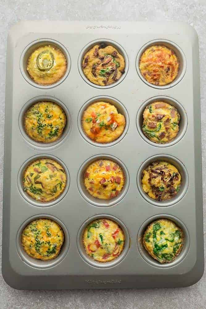 12 Cooked Breakfast Egg Muffins Inside of a Greased Muffin Pan on a Countertop