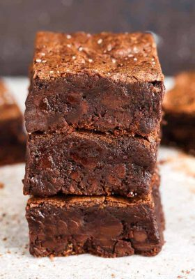 Side view of stacked Low Carb Paleo Keto Brownies on parchment paper