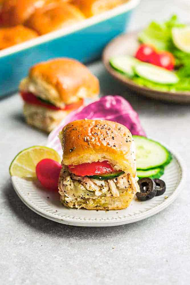 Buffalo Chicken Slider on a plate with cucumbers, tomato and olives