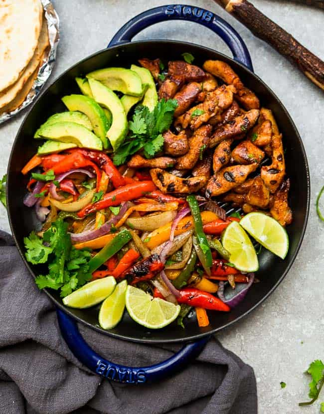 Top view of Keto Chicken Burrito Bowls in a blue skillet with chicken, avocado, bell peppers and lime