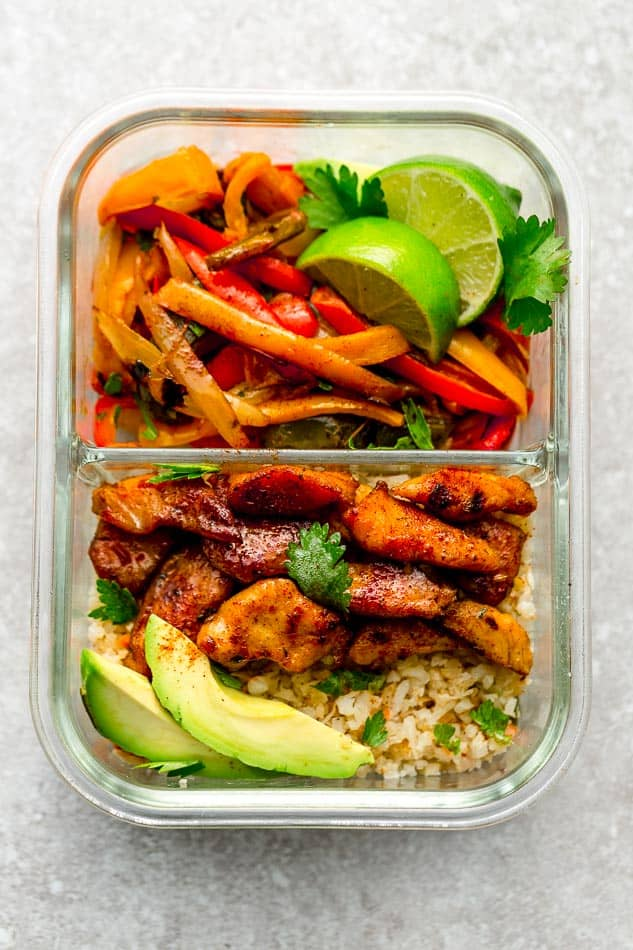 Top view of Keto Chicken Burrito Bowls in a meal prep container with cauilfower rice, lime and avocado