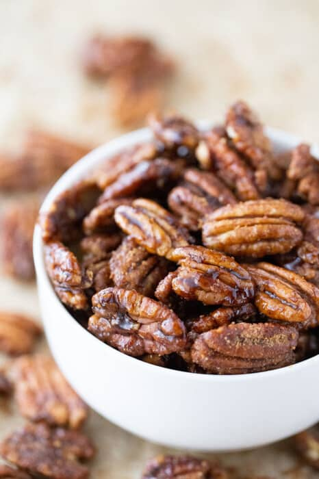 Close-up side view of a pile of easy candied pecans in a white bowl