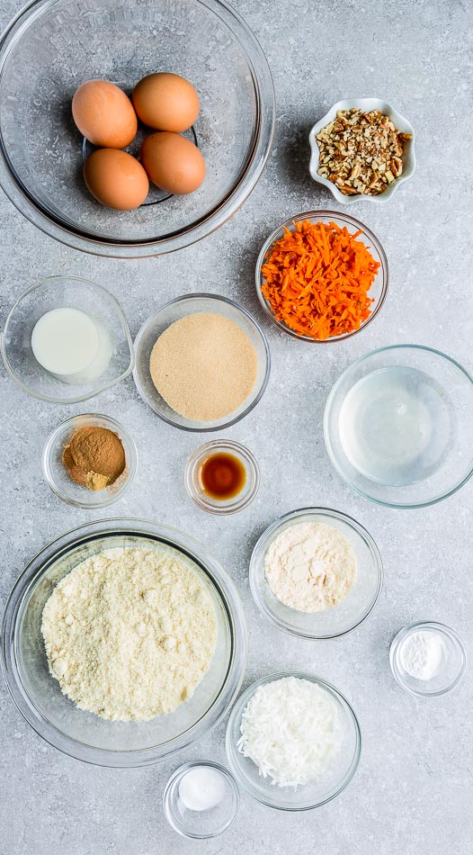 Top view of carrot cake ingredients in clear white bowls on a grey background