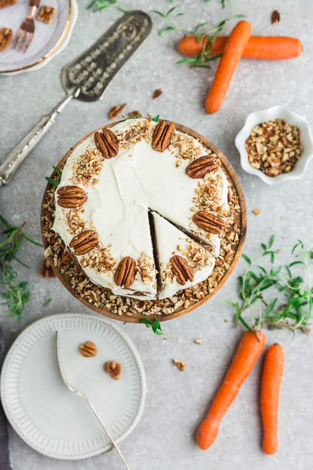 Top view of Keto Carrot Cake on wooden cake stand with chopped pecans and carrots