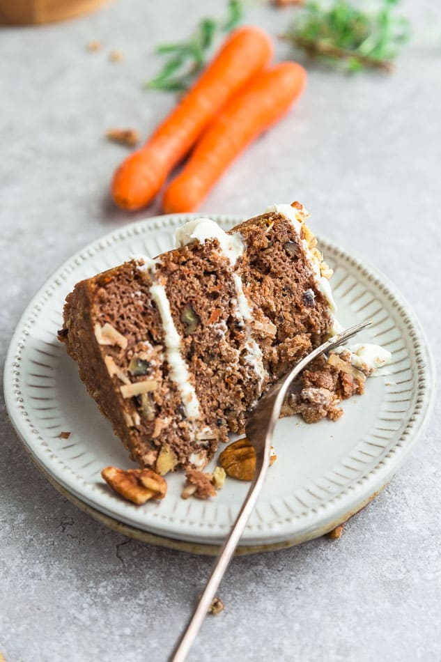 Close up of Low Carb Carrot Cake slice with a fork on a white plate