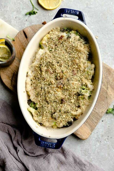 Top view of unbaked keto cauliflower gratin in a blue oval casserole dish on a wooden board