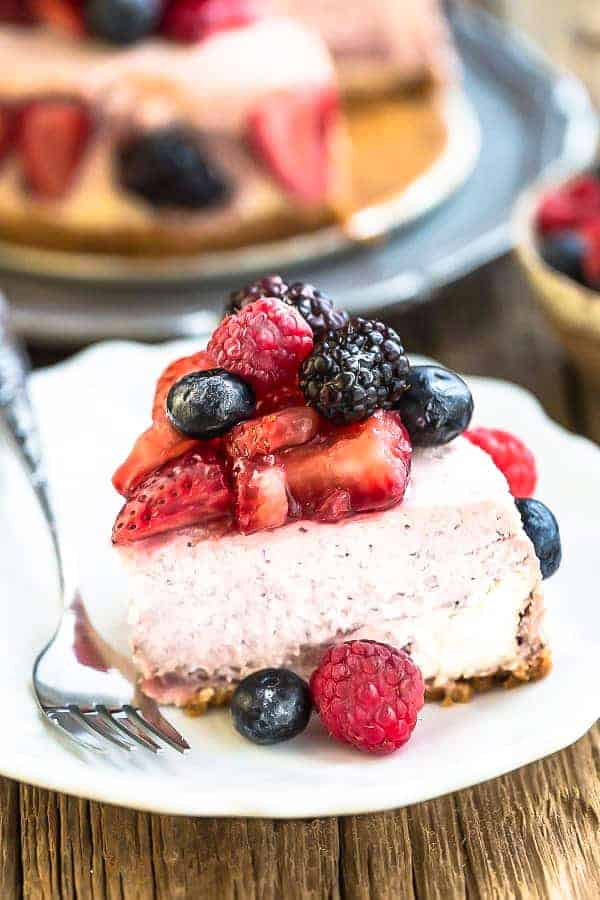 Top view of slice of Keto Cheesecake decorated with mixed berries on a white plate with a fork