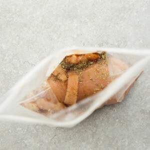 Top view of one chicken breast marinated chicken breast in ziplock bags