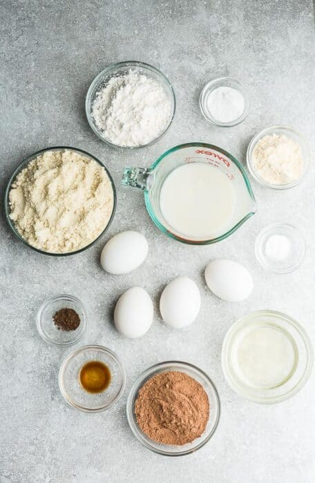 Top view of ingredients to make keto chocolate cake on a grey background