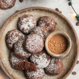 Top view of keto chocolate cookies in a beige bowl with powdered monk fruit sweetener, cocoa powder and christmas lights around the bowl on a grey background