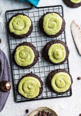 Top view of six keto chocolate fudge cookies with matcha green frosting on a wire rack with chocolate chips on the side