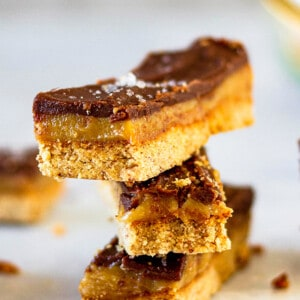 Front view of stacked chocolate peanut butter bars on a white background