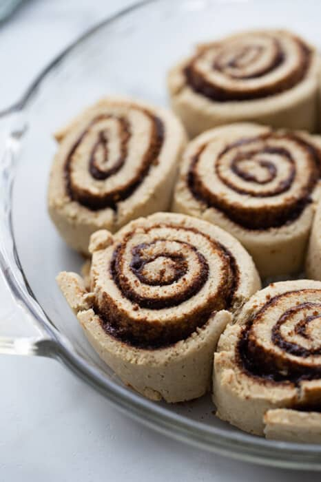 Close-up of raw cinnamon rolls in a glass pie dish