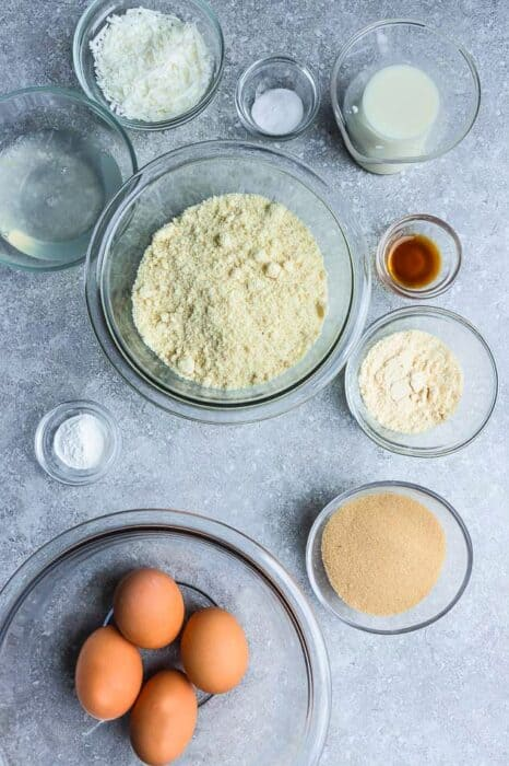 Top view of small bowls of ingredients to make coconut flour pancakes on a grey background