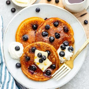 Top view of fluffy Keto blueberry pancakes on a white plate with a fork