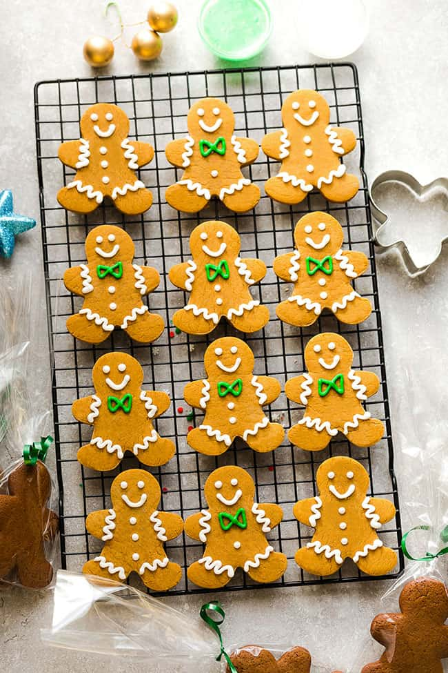 A dozen decorated gingerbread man cookies on a cooling rack