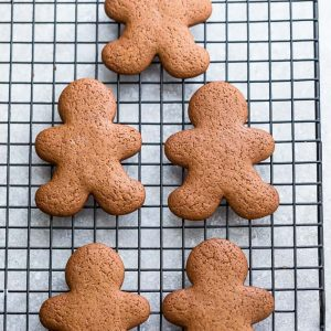 Top view of 4 plain gingerbread men cookies on a cooling rack