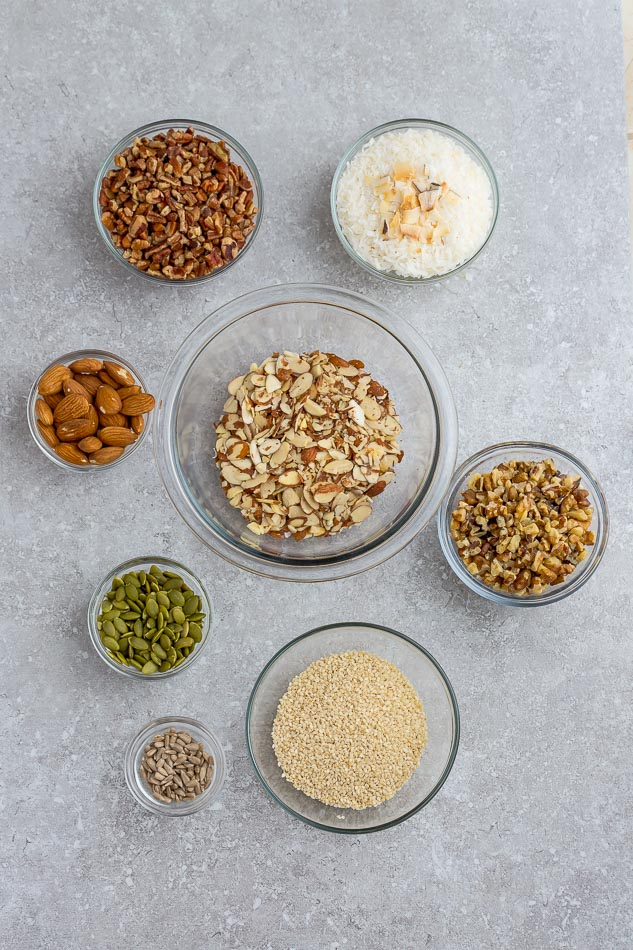 Top view of ingredients to make healthy granola on a grey background