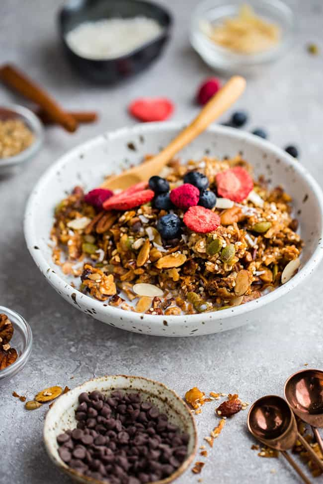 Side view of healthy granola in a white bowl on a grey background
