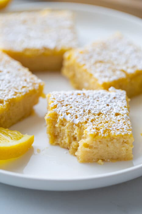 Side view of gluten free lemon bars on a white plate with a missing bite