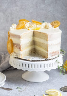 Side view of one low carb lemon cake on a white cake stand with one slice cut out