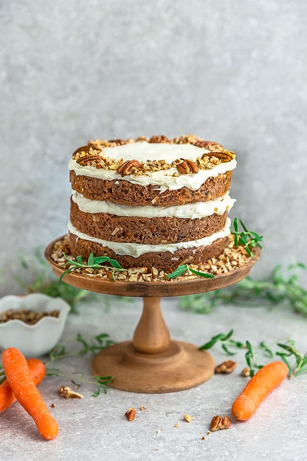 Side view of Keto Carrot Cake on wooden cake stand with chopped pecans and carrots
