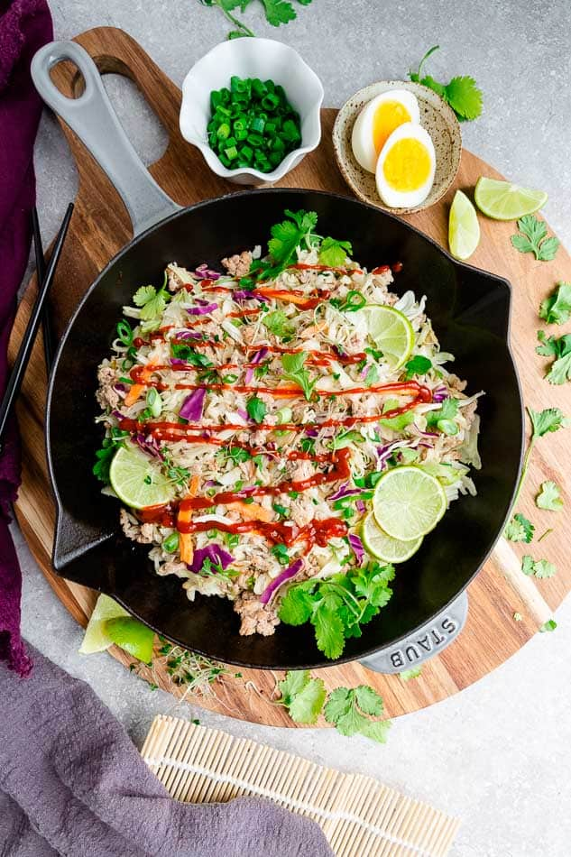 Overhead view of Egg Roll in a Bowl filling in a skillet topped with lime slices and drizzled with sauce
