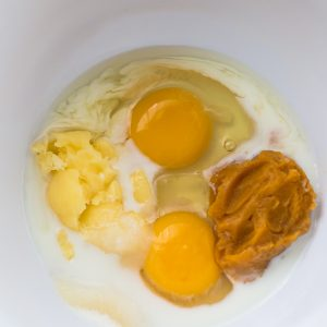 Top view of wet ingredients in a white bowl to make keto pumpkin pie
